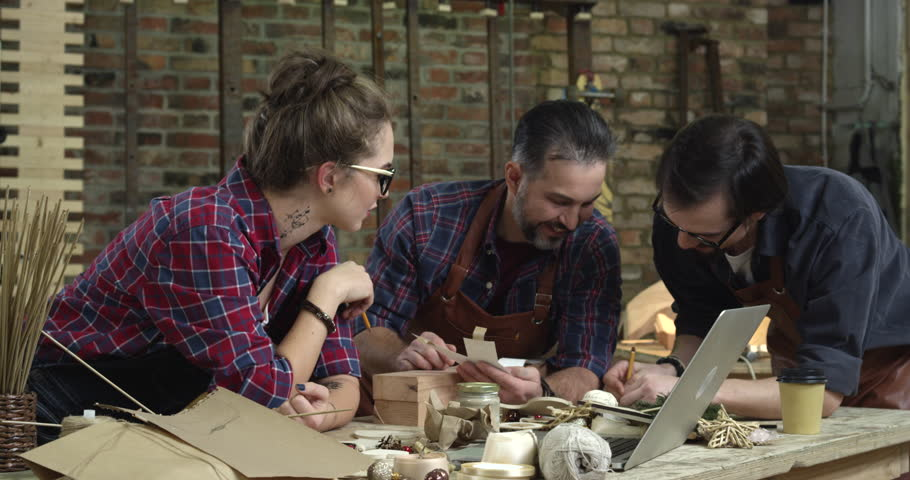 The mature master comes to listen to advice of younger designers to make a cabrioli leg for the table. Their workshop is very stylish/The Designer Determines the Form of Cabriole Legs for Table | Shutterstock HD Video #25632242