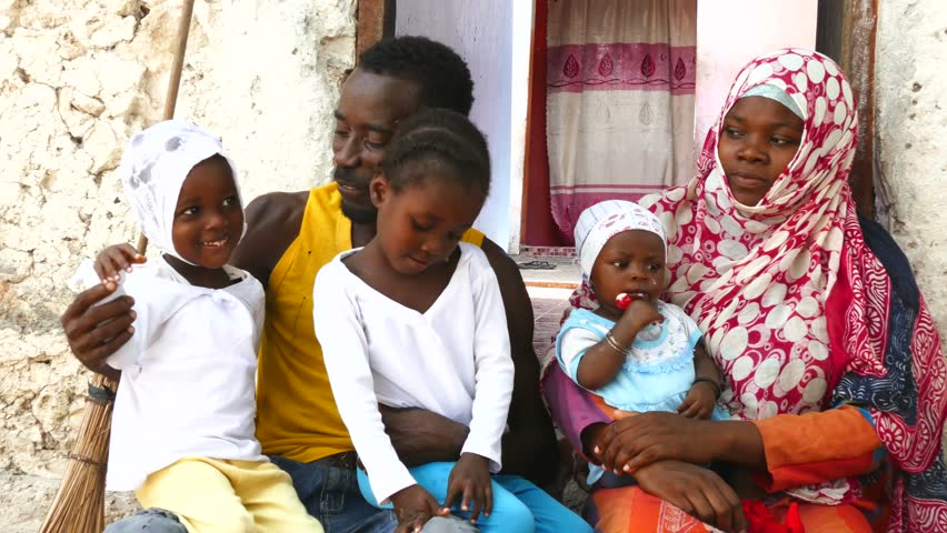 Happy African black family sitting in front of the house. Mother , father and three little daughters