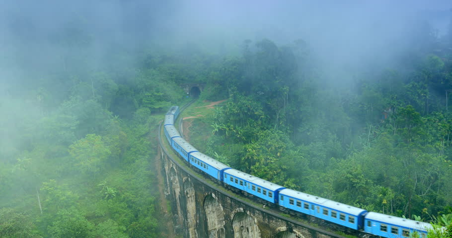 Train crossing Nine Arches Bridge and enters tunnel in foggy morning with clouds of mist above mountains overgrown with green tropical forest in Ella Sri Lanka