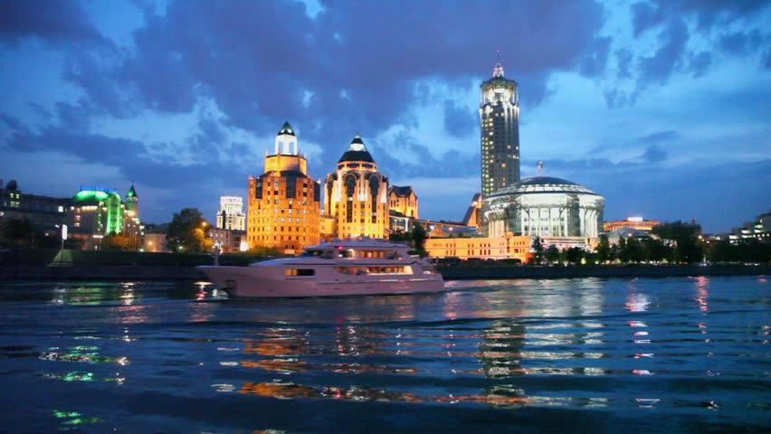Two ships float down the river near house of music located on quay at night in Moscow