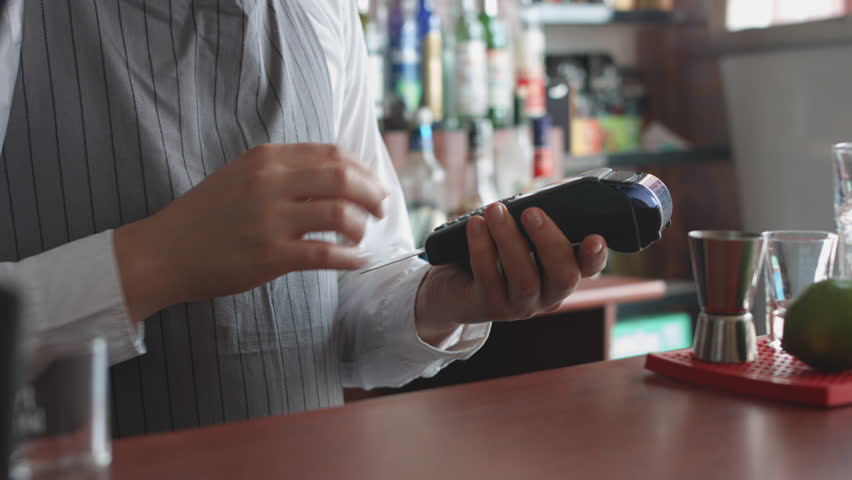 Man working in the bar accepting customer's cashless payment with credit card