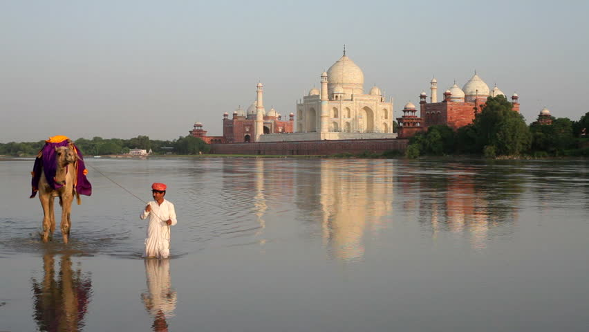 UTTER PRADESH, INDIA - CIRCA MAY 2011: Taj Mahal, UNESCO World Heritage Site, across the Jumna Yamuna River, Man leading camel