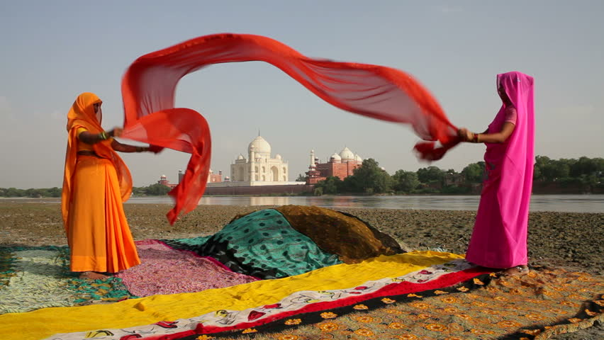 UTTER PRADESH, INDIA - CIRCA MAY 2011: Taj Mahal, across the Jumna Yamuna River, Women drying colourful Saris