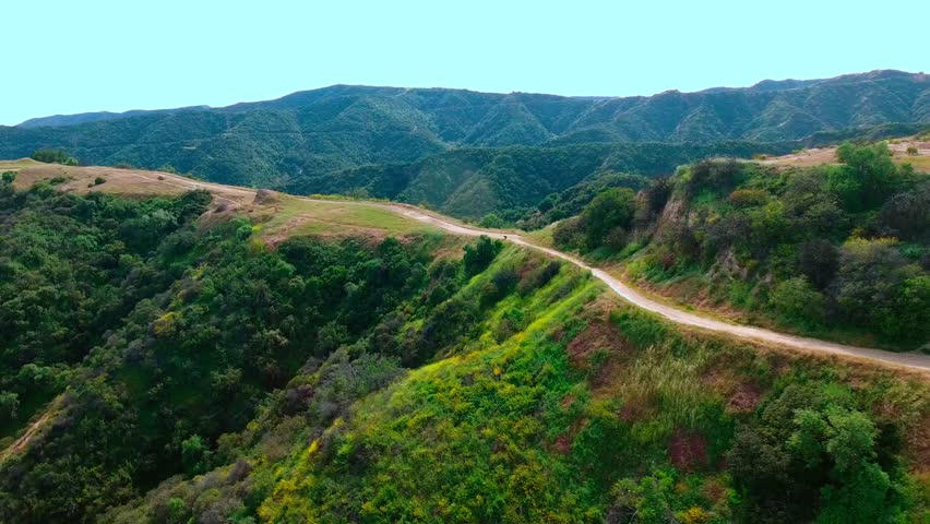 Aerial view of trail on top of lush green hills with a mountainous horizon | Shutterstock HD Video #25711691