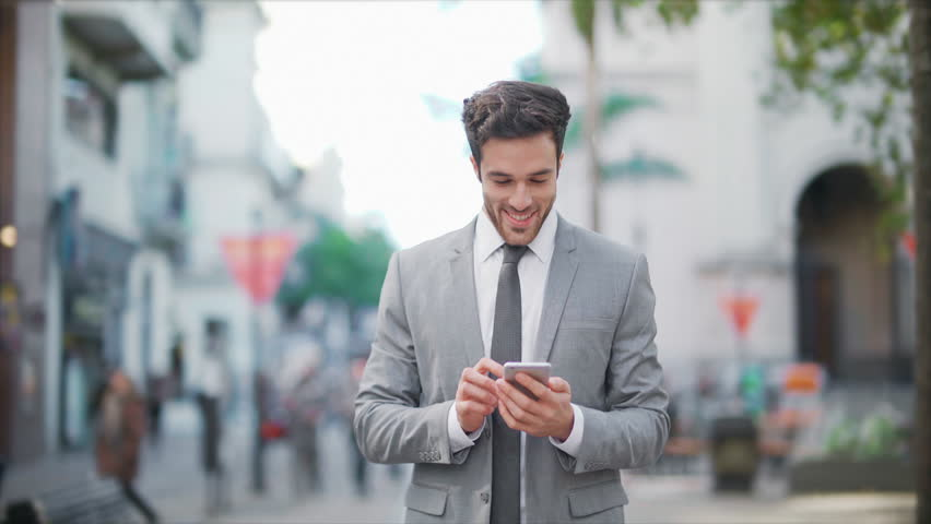 Cheerful businessman using a cell phone in a crowded street. He is checking mails, chats or the news online while walking.