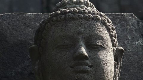 Close-up of head of meditating Buddha's statue carved from dark volcanic rock and illuminated by sun. Sculptural detail of Borobudur Buddhist temple, Magelang, Central Java, Indonesia. Panning video.