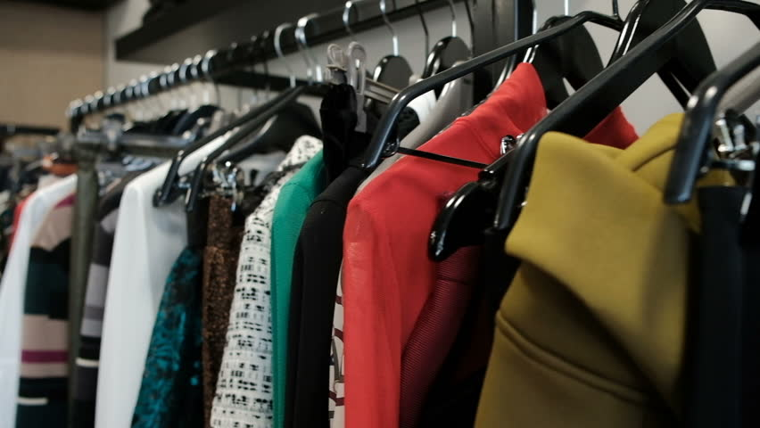 Shooting clothes in store, long line with black hangers with dresses. skirts, coats, sweaters, jackets, pants, blouses of different materials. Wool silk leather satin, multi-colored fabrics trimmed | Shutterstock HD Video #25734566