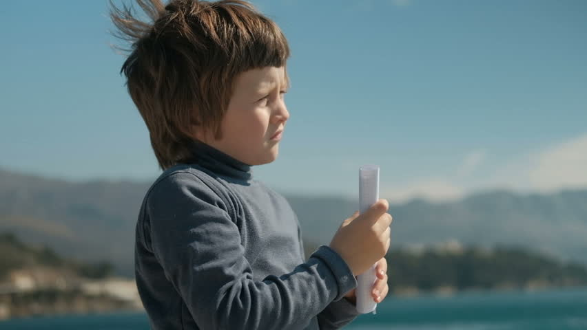 Boy folded piece of paper looking into the distance like trumpet to mountains. Slow motion picture of child standing on lake holding hands with paper in cage, like telescope, closed right eye, looks