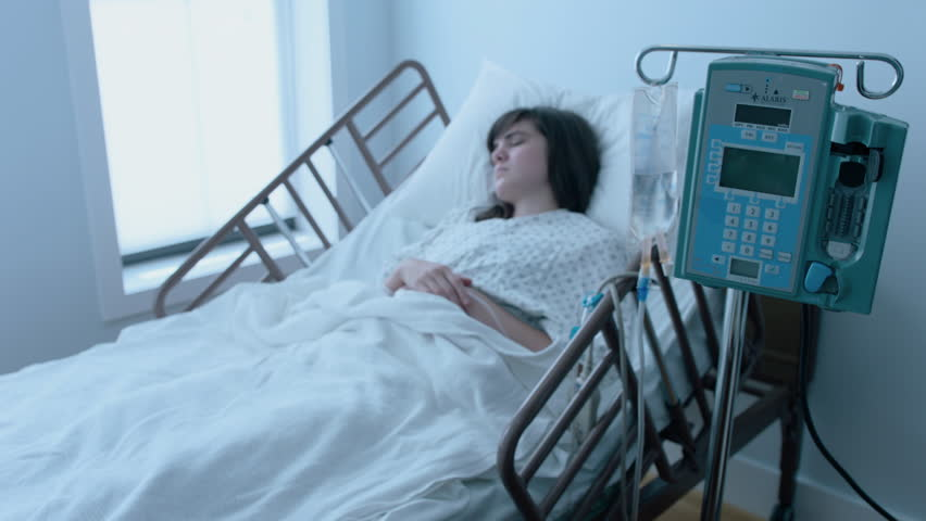 A sick young woman with an IV recovering in a hospital bed next to a window, slow motion, 4K | Shutterstock HD Video #25746611
