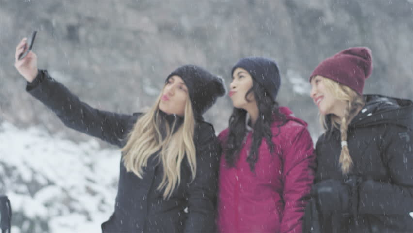 Three young beautiful ladies taking a selfie together on a snowy day #25753295