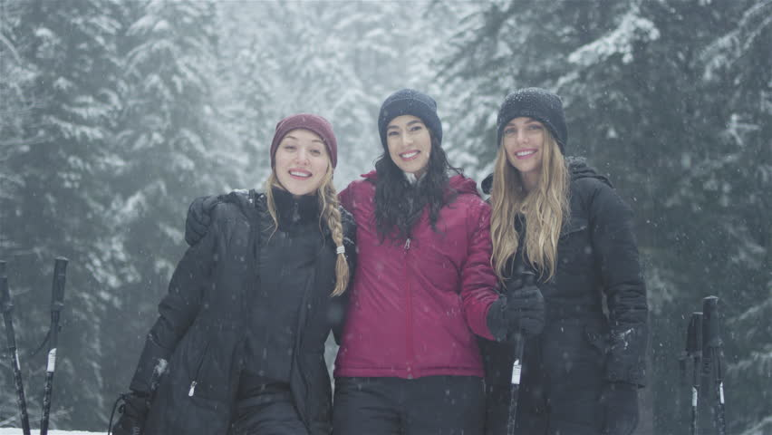 Portrait shot of three young ladies embracing, and smiling at the camera on a snowy day #25753355