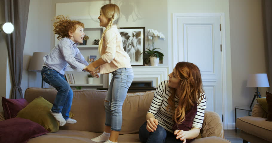 Little boy and girl jumping holding hands on the couch. Little boy and girl with their mother spending time together. Mother with kids having fun on sofa in the living room. Sister and brother.Indoors