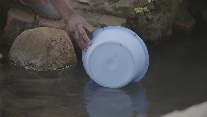 Malawi - November 2016: Woman collects water from an open source well   Shutterstock HD Video #25777451