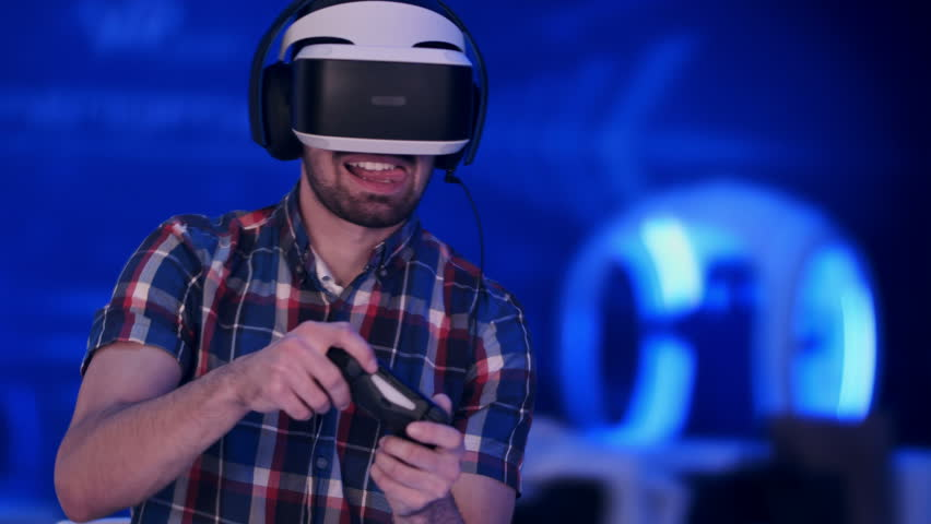 Happy young man with virtual reality headset with controller gamepad playing racing video game   Shutterstock HD Video #25784966