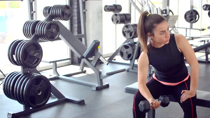 Attractive fitness woman lifting weights in gym. | Shutterstock HD Video #25785650