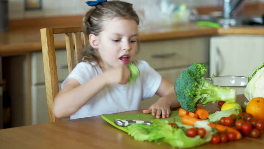 Girl eating broccoli sitting at the kitchen table. vegetarianism, healthy living,healthy vegetables, healthy food, baby food, Wellness, kitchenware, mother's assistant, food preparation #25795916
