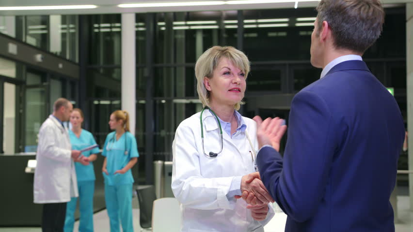 Female doctor shaking hands with businessman in corridor at hospital   Shutterstock HD Video #25810646