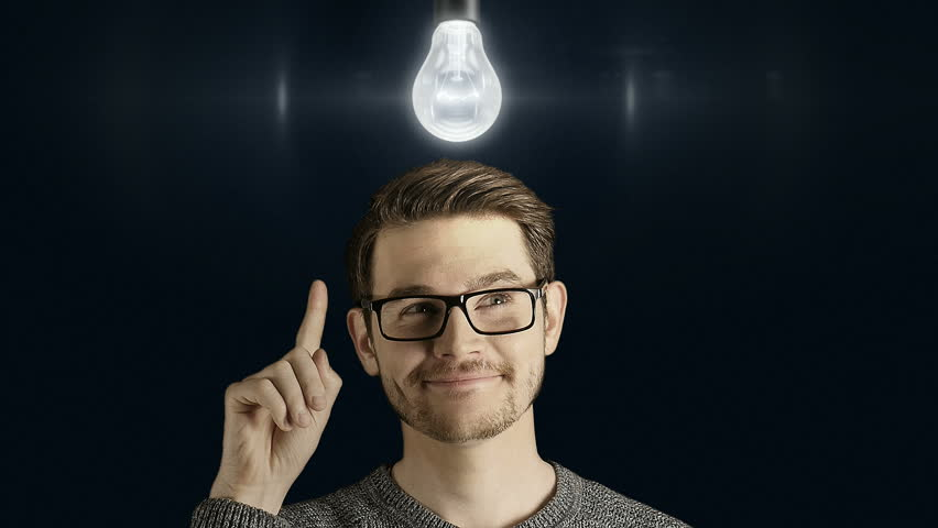 Clever creative man think gets an idea, which lights up a symbolic lamp over his head on dark background
