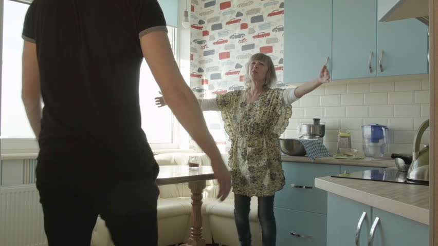 Adult son hugging his mother in the kitchen