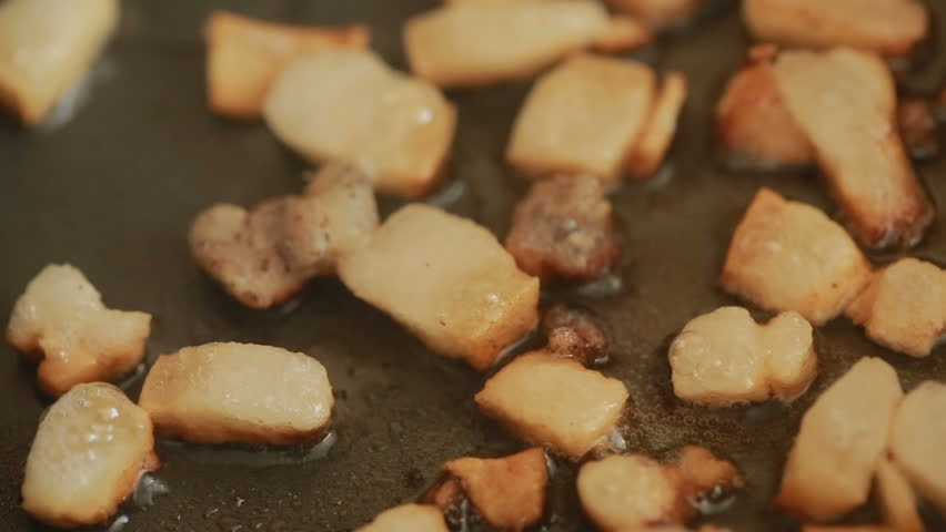 Bacon pieces on a hot frying pan are toasted | Shutterstock HD Video #25816229
