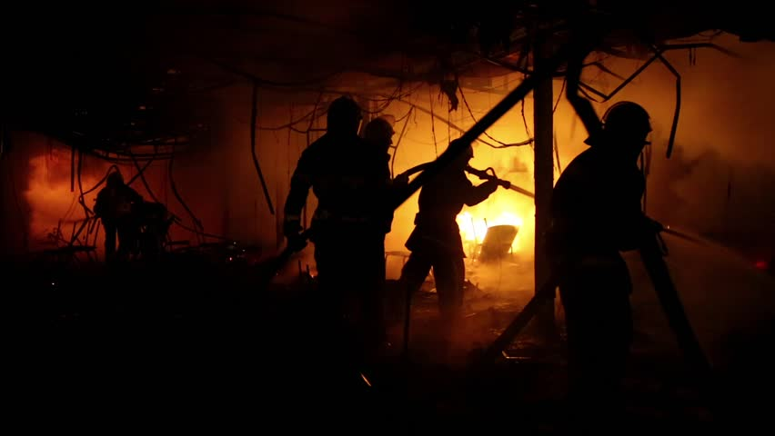 Brave firemen inside burning building. Fire extinguishing, fire brigade inside burning premises. House destroyed by fire