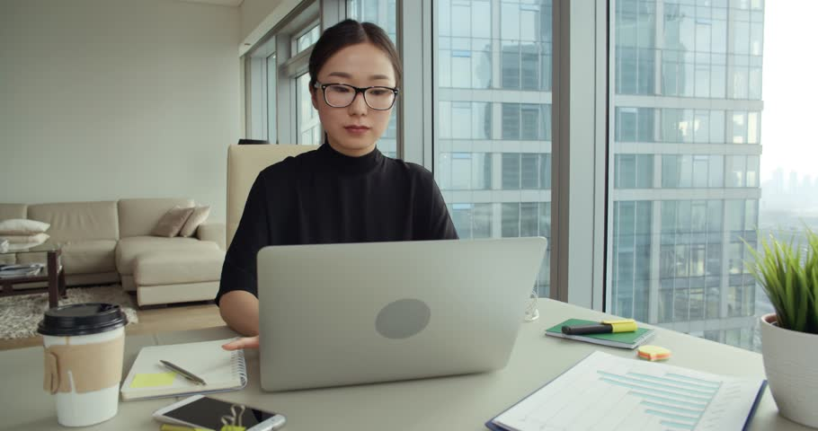 successful young Asian girl in a modern office skyscraper, the work environment, Steadicam shot