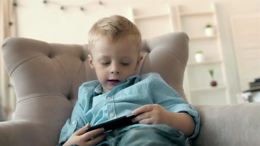 Boy with smartphone at home playing, game on phone