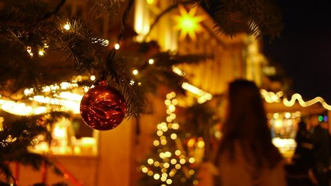 Shoppers at an open-air market at christmas. Foreground is a christmas tree. Shoppers are blurred. Nightime.