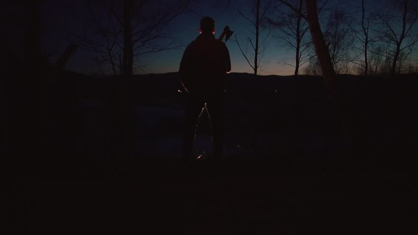 The back silhouette of the man holding the ax on his shoulder in the dark forest.
