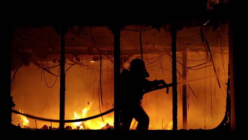 Fire extinguishing, fire brigade inside burning premises. Brave firemen inside burning building. House destroyed by fire