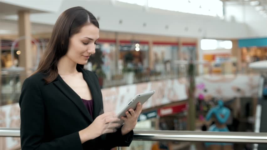 Young female passenger traveller at the airport using her tablet computer while waiting for flight, business woman after work in office in shopping mall use tablet pc | Shutterstock HD Video #25864988
