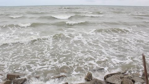 Big waves and heavy wind hit the rock beach