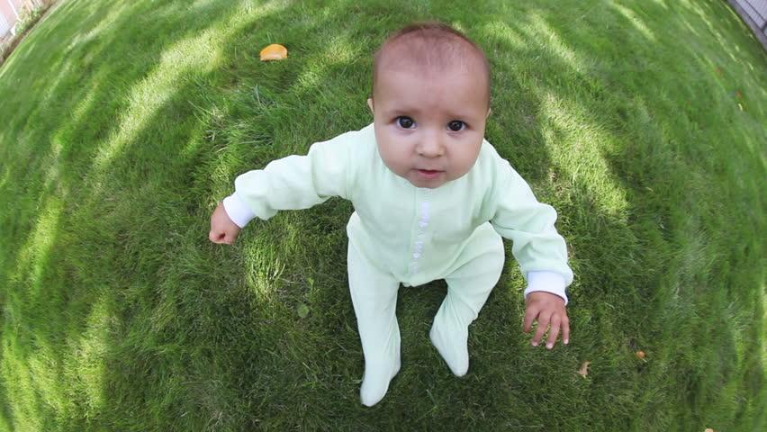 Adorable sitting toddler on lawn of garden, fisheye #2587364