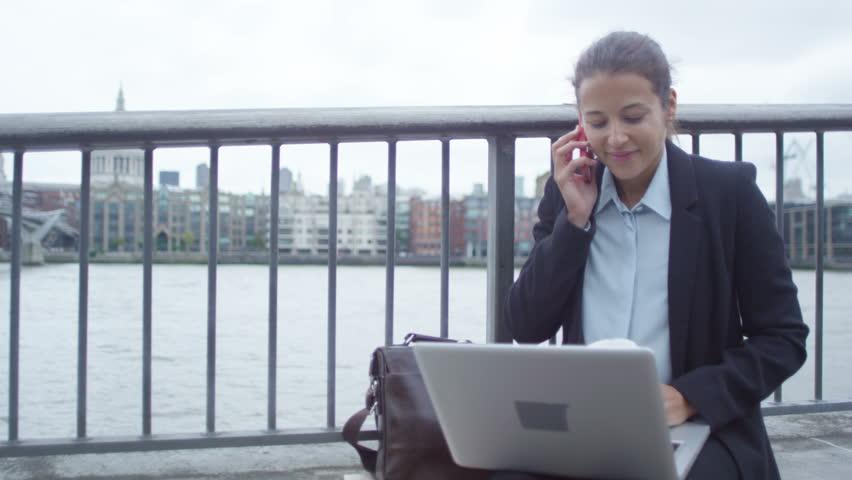4K Smiling London businesswoman using laptop & talking on phone outdoors in city | Shutterstock HD Video #25874063