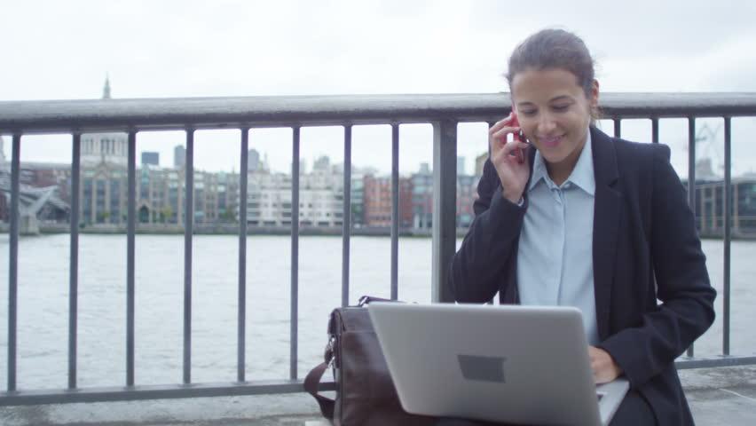 4K Smiling London businesswoman using laptop & talking on phone outdoors in city | Shutterstock HD Video #25874234