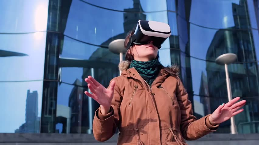 a young woman in the virtual glasses in the open air