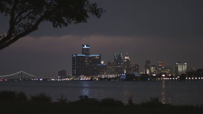 DETROIT, MI - CIRCA 2014: Establishing shot of the city skyline at night from Belle Isle looking across the Detroit River.  Close view with silhouetted foreground and overcast sky.