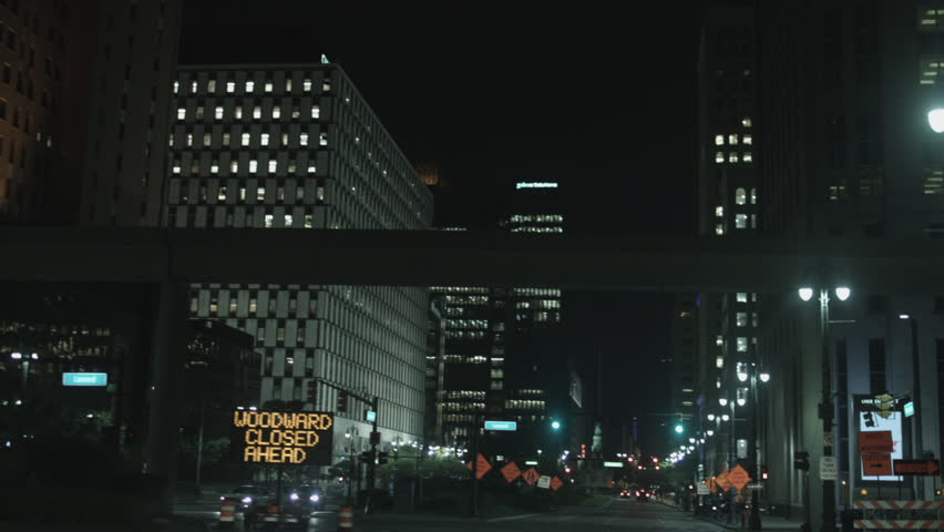 DETROIT, MI - CIRCA 2014: Driving plate: front view. Jefferson Ave turn on to Woodward in down town at night past high-rise commercial property.  Mid West USA, overcast.  24mm lens, stabilized