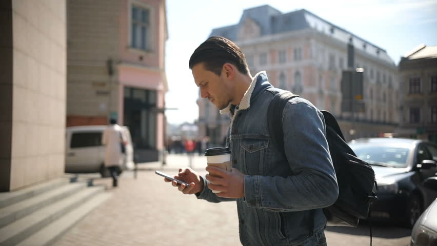 Young attractive man walks down the street holding coffee and using phone