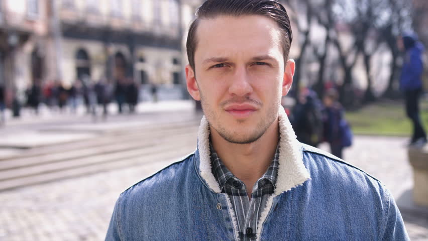Portrait of attractive serious stylish young man looking into the camera and smiling in the city | Shutterstock HD Video #25903028