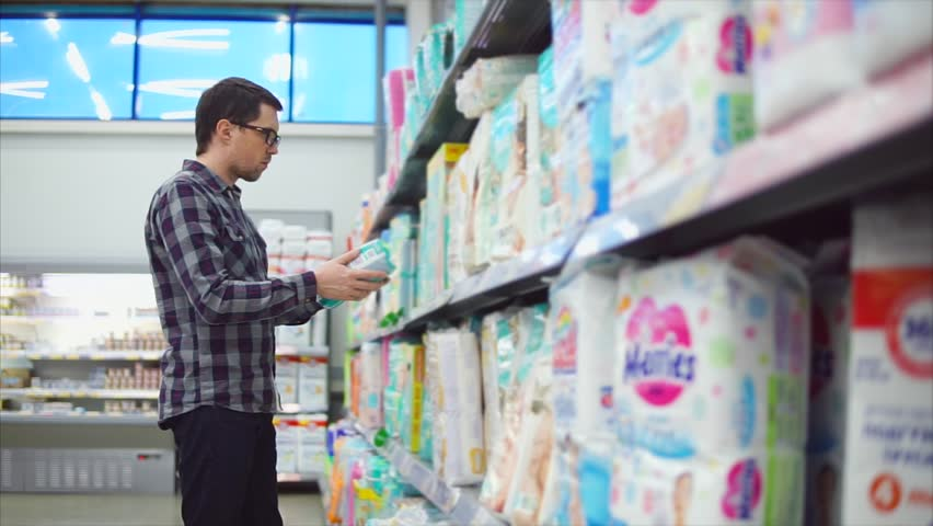 A serious man in glasses, dressed in a plaid shirt examines diapers in the children's department of the hypermarket. A person considers children's belongings for his little child. #25906250