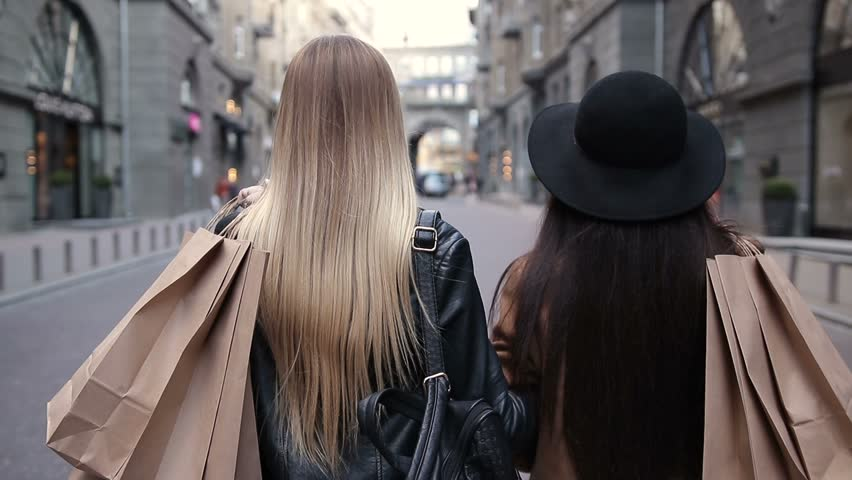 Back view of two walking women with shopping bags #25947062