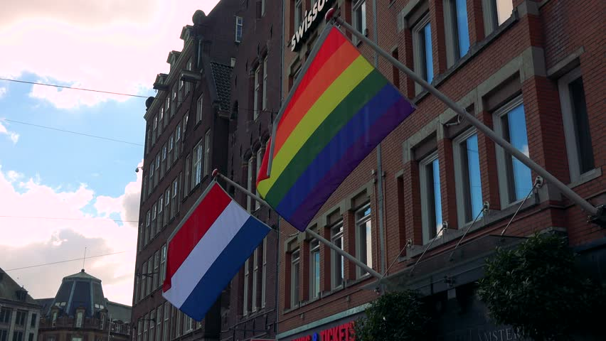 AMSTERDAM, NETHERLANDS - AUGUST 9, 2016: The Rainbow Flag and the flag of the Netherlands hang from poles fixed on a building and sway in the wind, the cloudy blue sky in the background | Shutterstock HD Video #25961426