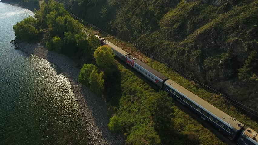 Lake Baikal oldest. Railways Russia Siberia. listvyanka. Passenger train rides near the water behind trees. Mountains. Summer sun shines blue water. Unique aerial video view from above train 4k