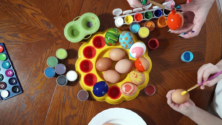 Mom and daughter are preparing for Easter. paint eggs. Top view | Shutterstock HD Video #25989311