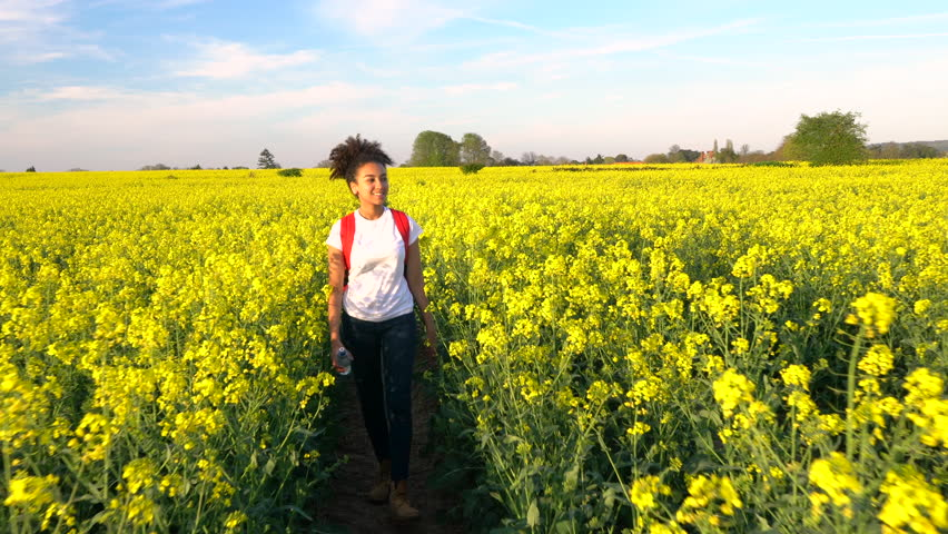 Beautiful happy mixed race African American girl teenager female young woman hiking with orange backpack and bottle of water in field of rape seed yellow flowers