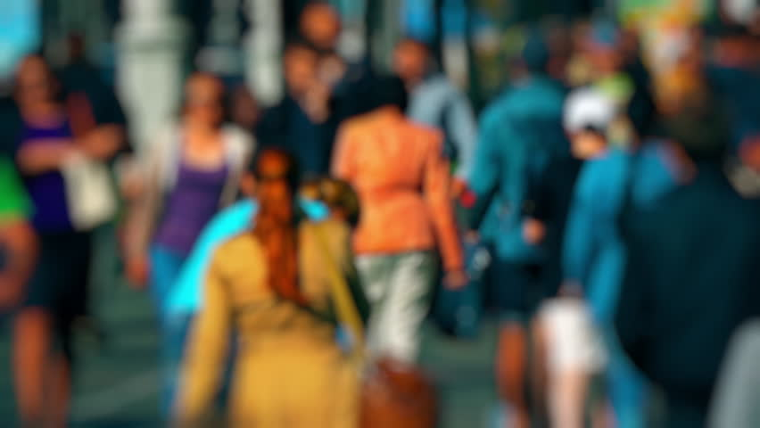 Mother with stroller in crowd. Anonymous crowd on a busy street. People talking cellphones walk down a busy street with green trees on a hot summer day. Slow motion. (av34123c)