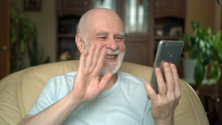 Good-looking handsome senior man sitting on chair at home. Using cellphone, talking via messenger | Shutterstock HD Video #25999733