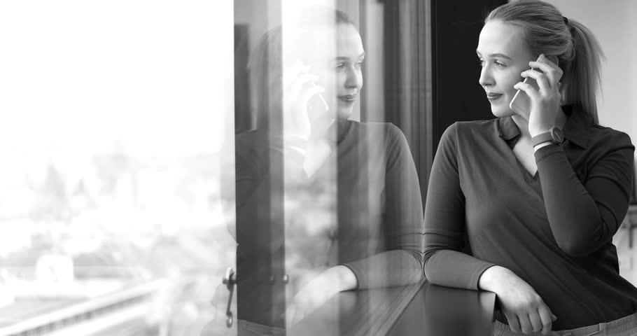 Elegant Woman Using Mobile Phone by window in office building | Shutterstock HD Video #26012348