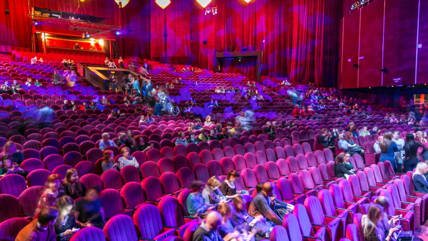 MOSCOW, RUSSIA - CIRCA JANUARY 2017: Spectators gather in the auditorium and watch the show in theatre timelapse. Large hall with red armchairs seats. Viewers filling places until turn off the light